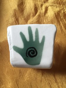 white stone with handprint. The handprint has a spiral on it. | Balanced Body Care